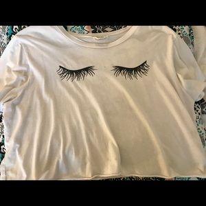White shirt with eyelashes and writing